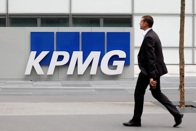 A man walks past a KPMG logo outside one of the accountancy firm's offices. Photo: Reuters/Charles Platiau