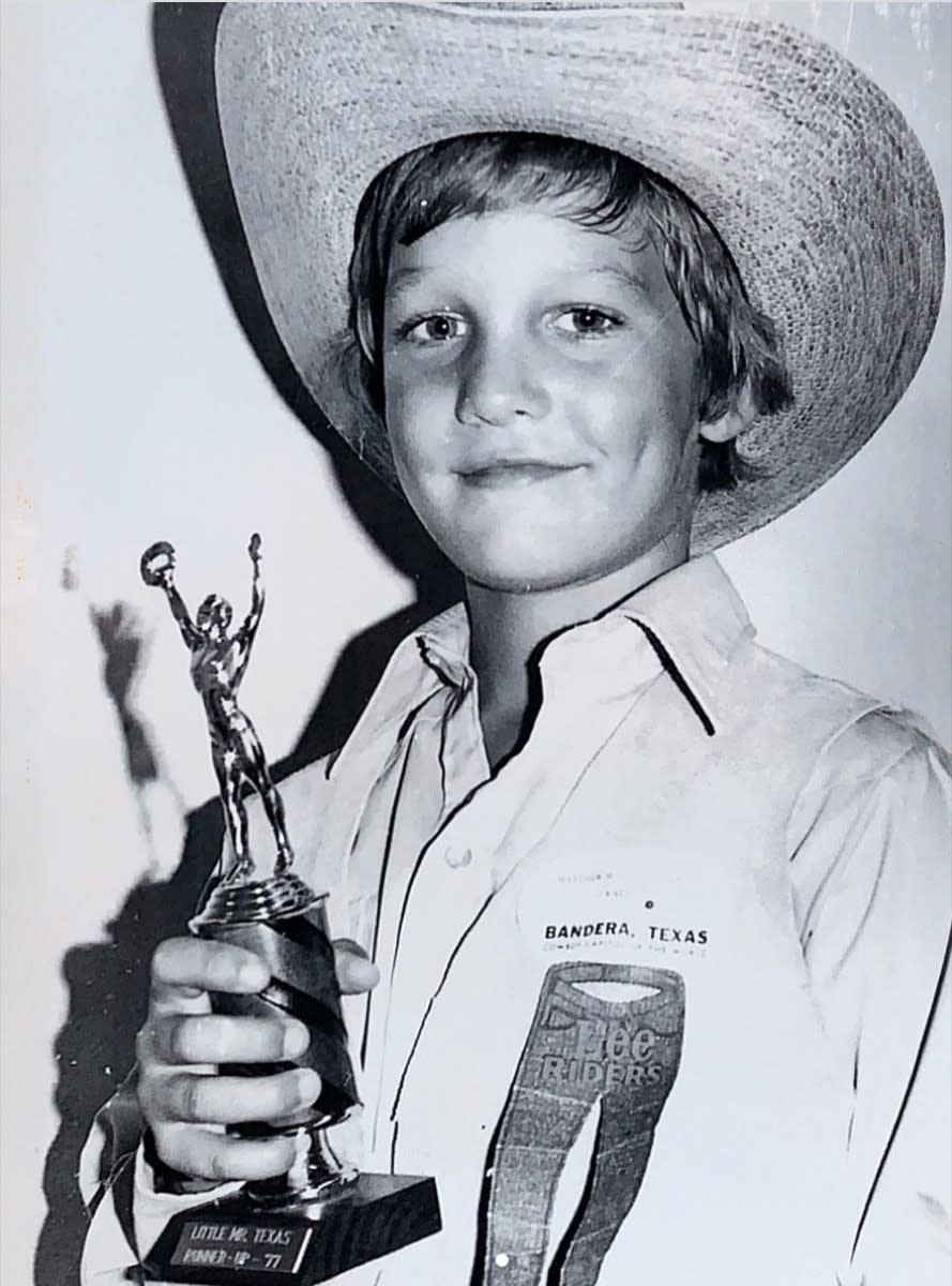 matthew mcconaughey as a child in a black and white photo wearing a cowboy hat and holding a trophy