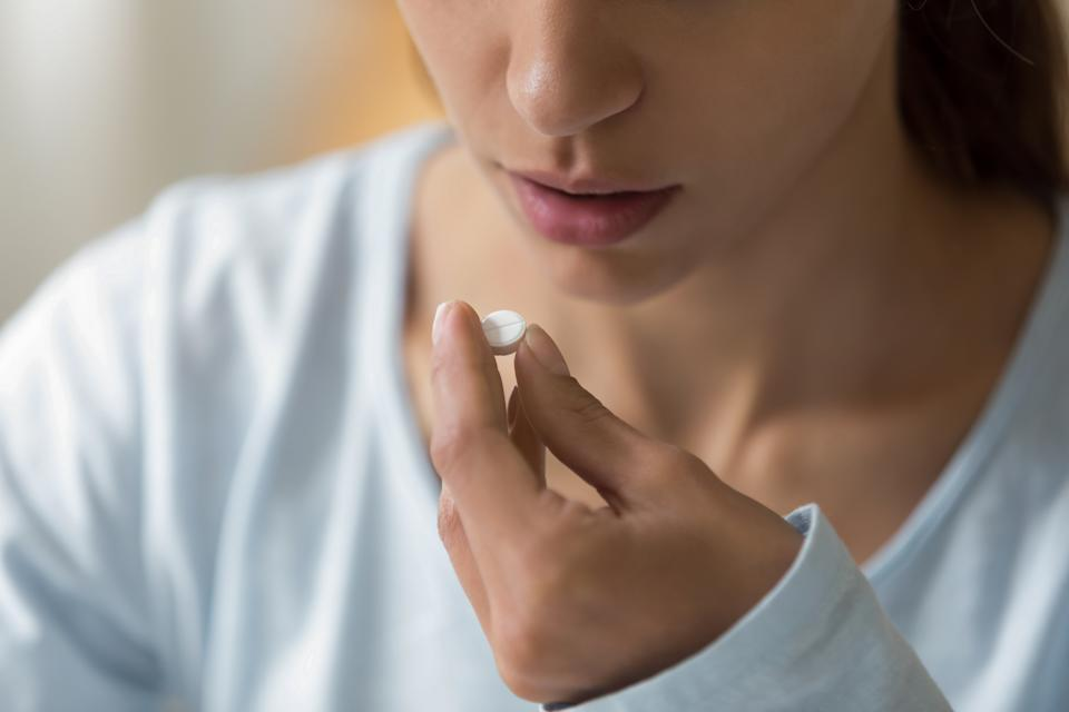 Closeup image of woman face and pill in hand. Sick young female holding white round pill near her mouth and going to take medication as per doctor prescription for recovery. Healthcare medical concept