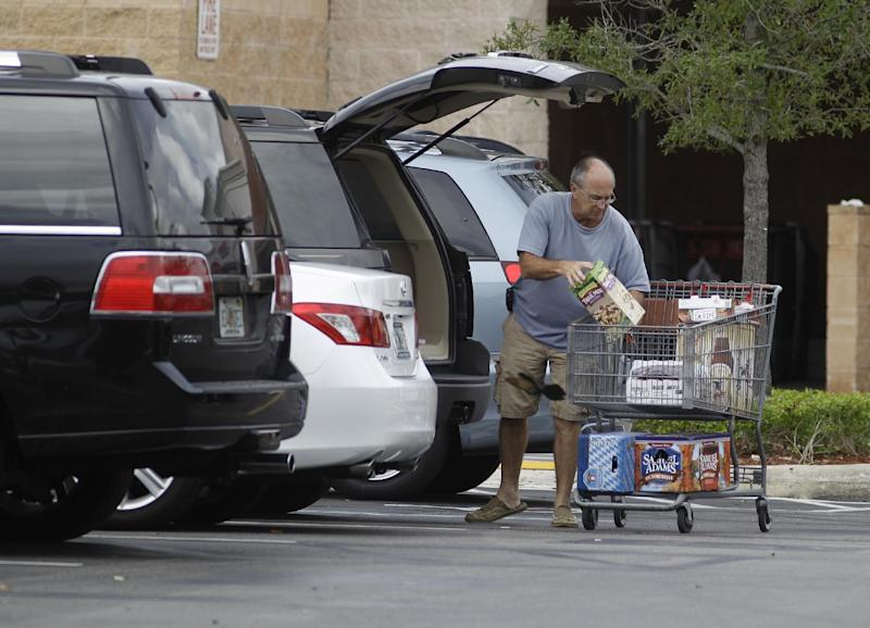 FILE - In this file photo taken Sept. 30, 2011, unidentified shoppers unload their shopping cart at a Pembroke Pines, Fla. Costco store. Costco Wholesale Corp.'s fiscal fourth-quarter net income climbed 11 percent as the wholesale club operator made more money on membership fees and saw its sales rise.  (AP Photo/J Pat Carter, File)