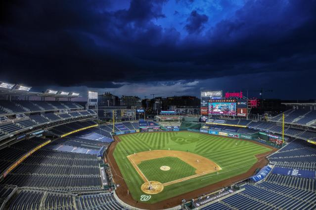 A storm brews over Nationals Park, where MLB's shortened 2020 season is scheduled to begin on Thursday night. (AP Photo/Alex Brandon)