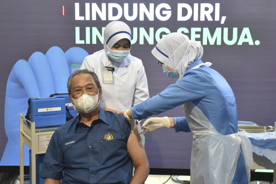 Malaysia's Prime Minister Muhyiddin Yassin receives the first dose of Pfizer-BioNTech COVID-19 vaccine at a clinic in Putrajaya, Malaysia, Wednesday, Feb. 24, 2021. (Malaysia Health Ministry via AP)