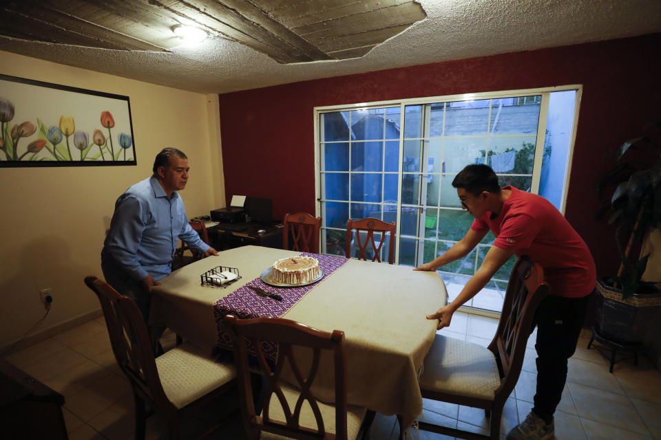 Alejandro Canejo Lopez, left, and his son Daniel, 16, move the dining room table so they can add an extra table to increase distancing between guests, as they prepare to celebrate the 15th birthday of Ximena Canejo Hernandez along with a small group of close relatives, in Tlalnepantla, just outside Mexico City, Monday, July 13, 2020. Ximena's family, wanting to give her a traditional Quinceanera, had booked a church and event hall for July 18 long before the coronavirus pandemic hit, but the celebration has now been postponed until late November.(AP Photo/Rebecca Blackwell)