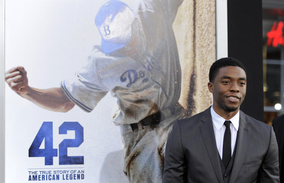 """FILE - In this Tuesday, April 9, 2013 file photo, Chadwick Boseman, who plays baseball legend Jackie Robinson in """"42,"""" poses at the Los Angeles premiere of the film at the TCL Chinese Theater in Los Angeles. Actor Chadwick Boseman, who played Black icons Jackie Robinson and James Brown before finding fame as the regal Black Panther in the Marvel cinematic universe, has died of cancer. His representative says Boseman died Friday, Aug. 28, 2020 in Los Angeles after a four-year battle with colon cancer. He was 43. (Photo by Chris Pizzello/Invision/AP, File)"""
