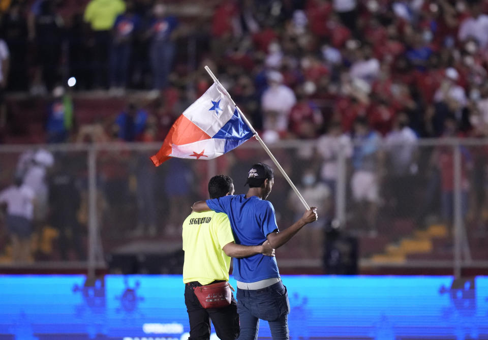 A security guard escorts a Panama fan off the field at the end of a qualifying soccer match against the United States for the FIFA World Cup Qatar 2022 at Rommel Fernandez stadium, in Panama city, Panama, Sunday, Oct. 10, 2021. Panama won 1-0. (AP Photo/Arnulfo Franco)