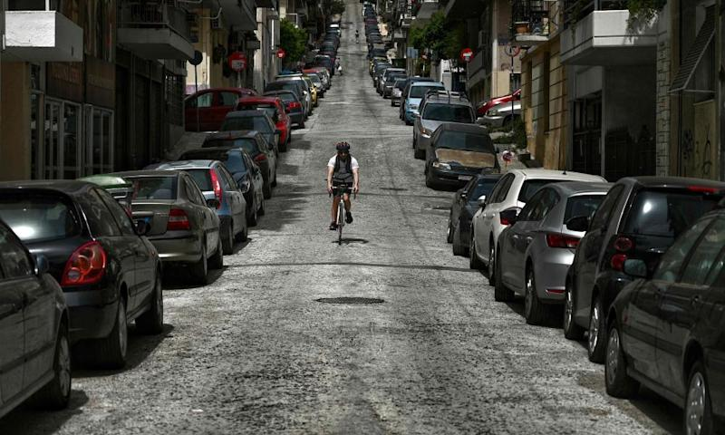 A cyclist rides down a deserted street in central Athens