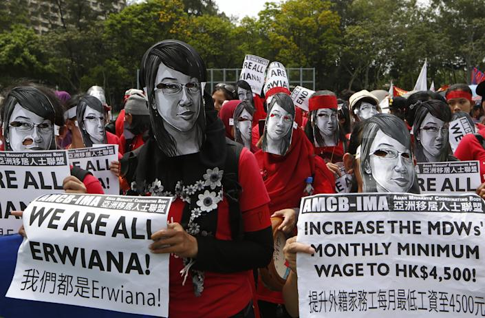 Domestic helpers and their supporters wear masks featuring the picture of Indonesian maid Erwiana Sulistyaningsih, who was allegedly brutally tortured by her employers, during a march to mark the May Day in Hong Kong, Thursday, May 1, 2014. The domestic helpers demanded to increase their monthly minimum wage to HK$4,500 (US$580). (AP Photo/Kin Cheung)
