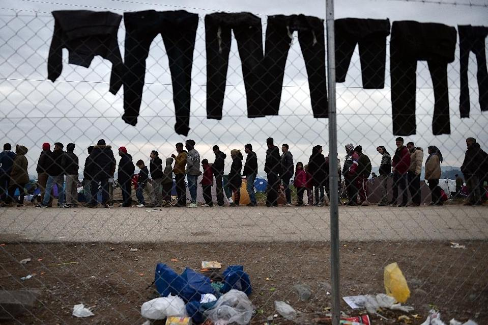 Refugees queue for food as trousers dry at the improvised camp near Idomeni, on February 28, 2016 (AFP Photo/Louisa Gouliamaki)