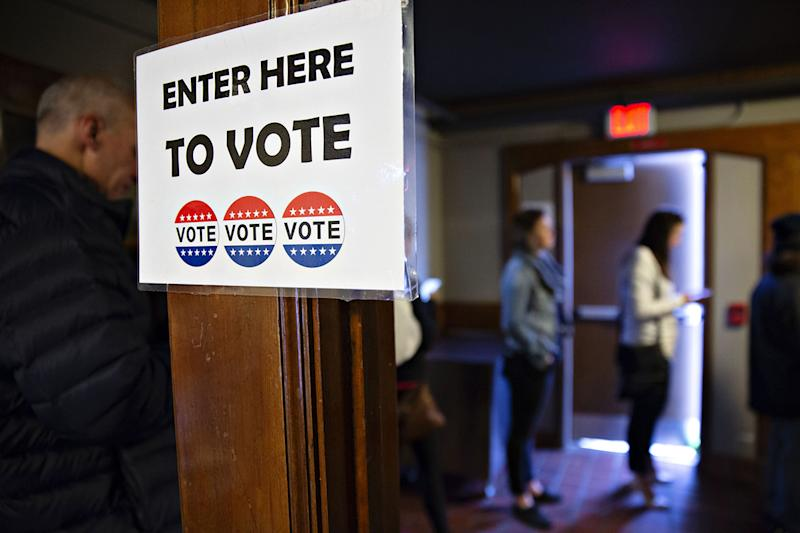 Voters wait in line to cast ballots at a polling station. (Credit: Daniel Acker/Bloomberg via Getty Images)