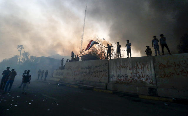 <p>TOPSHOT – Iraqi protesters wave a national flag while demonstrating outside the burnt-down local government headquarters in the southern city of Basra on September 7, 2018 during demonstrations over poor public services. – Basra has seen a surge in protests since September 4, with demonstrators torching government buildings as well as political party and militia offices, as anger boils over after the hospitalisation of 30,000 people who had drunk polluted water. (Photo by Haidar MOHAMMED ALI / AFP) (Photo credit should read HAIDAR MOHAMMED ALI/AFP/Getty Images) </p>