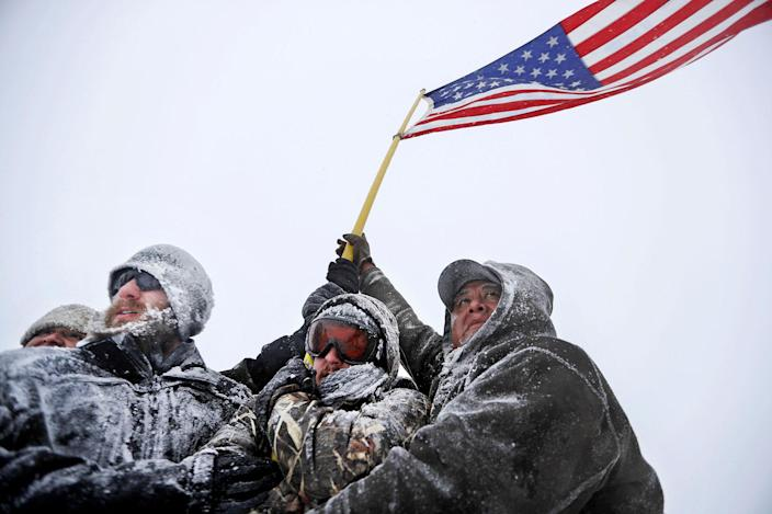 <p>DEC. 5, 2016 — Military veterans huddle together to hold a United States flag against strong winds during a march to a closed bridge outside the Oceti Sakowin camp where people have gathered to protest the Dakota Access oil pipeline in Cannon Ball, N.D. (AP Photo/David Goldman) </p>