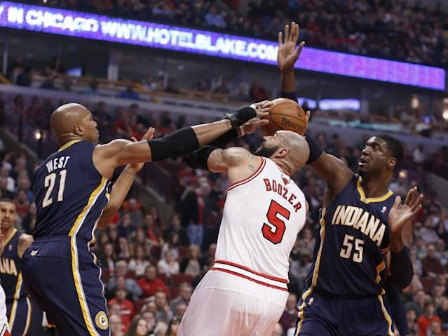 Indiana Pacers forward David West (21) and Roy Hibbert (55) pressure Chicago Bulls forward Carlos Boozer (5) during the first half of an NBA basketball game Monday, March 24, 2014, in Chicago. (AP Photo/Charles Rex Arbogast)