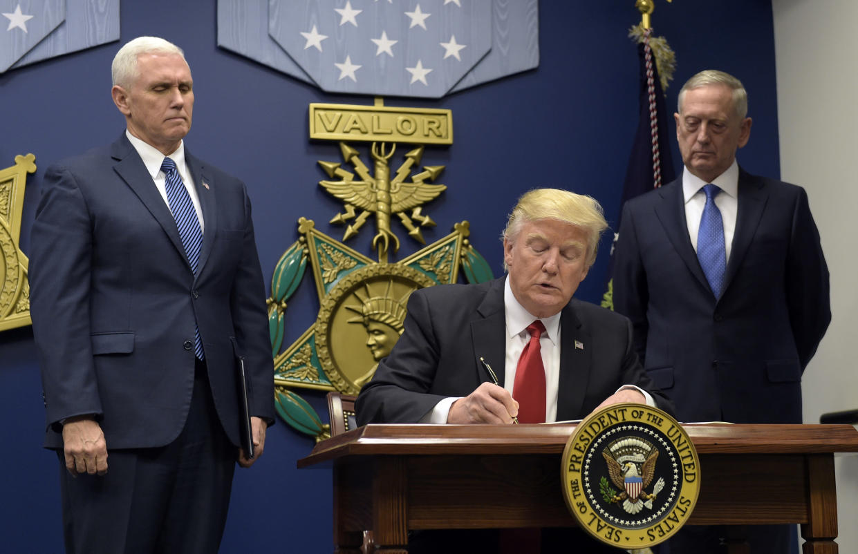 President Trump, with Vice President Mike Pence, left, and Defense Secretary James Mattis, signs an executive action on extreme vetting, Jan. 27, 2017. (Photo: Susan Walsh/AP)