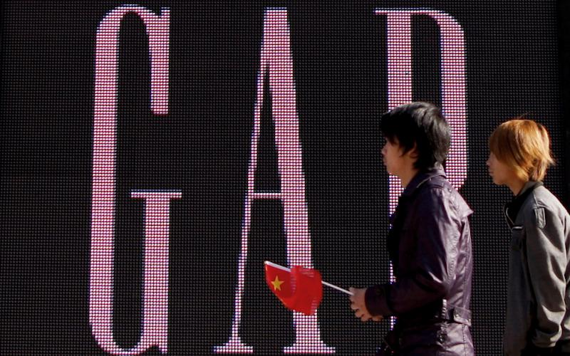 A man carries a Chinese flag as he walks past a GAP store in Beijing - AP
