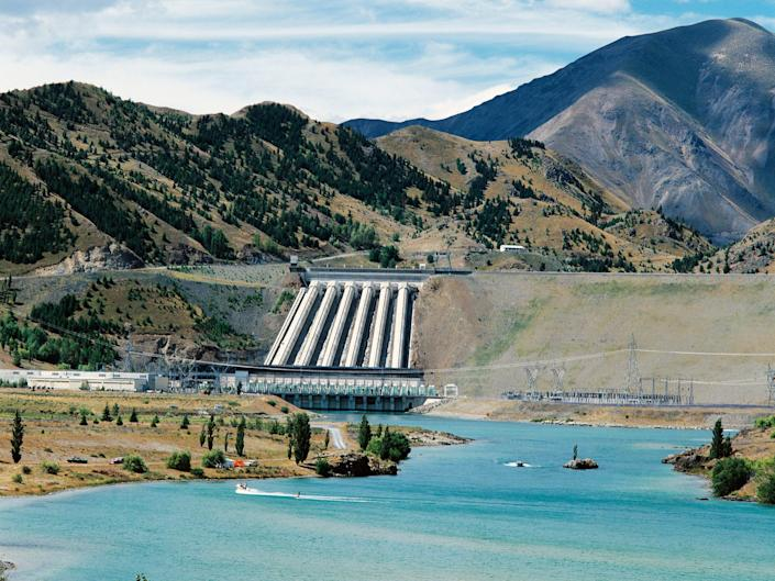 A hydroelectric plant sits in New Zealand along a mountain range and blue skies.