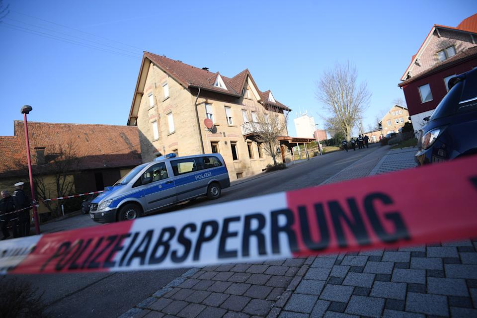 24 January 2020, Baden-Wuerttemberg, Rot Am See: After shots were fired in Rot am See in northeastern Baden-Wuerttemberg, a police car is standing behind a barrier at a house. Several people are said to have been killed here. A suspect has been arrested, the police said. Photo: Marijan Murat/dpa (Photo by Marijan Murat/picture alliance via Getty Images)