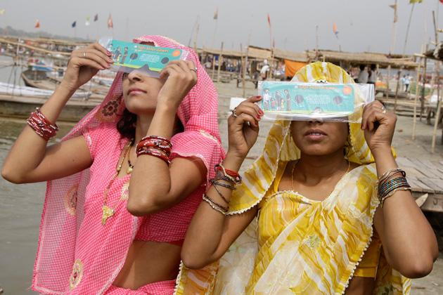 Women use eclipse glasses to watch Venus passing in front of the sun in the northern Indian city of Allahabad June 6, 2012. The planet Venus made a slow transit across the face of the sun on Tuesday, the last such passing that will be visible from Earth for 105 years. Picture taken June 6, 2012. REUTERS/Jitendra Prakash