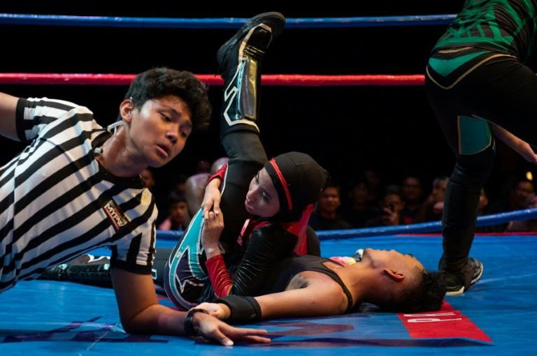 Far from being criticised by conservatives for throwing herself into wrestling, this 19-year-old Malaysian woman has become a hit on social media (AFP Photo/Mohd RASFAN)