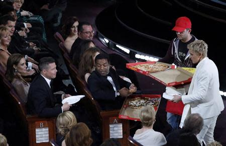 Show host Ellen DeGeneres delivers pizza to the audience at the 86th Academy Awards in Hollywood, California March 2, 2014. REUTERS/Lucy Nicholson