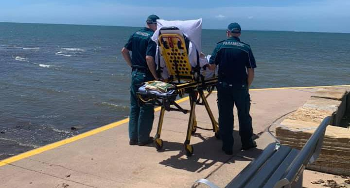 Two Queensland Ambulance paramedics stand with a patient on a stretcher at the Cleveland Lighthouse.