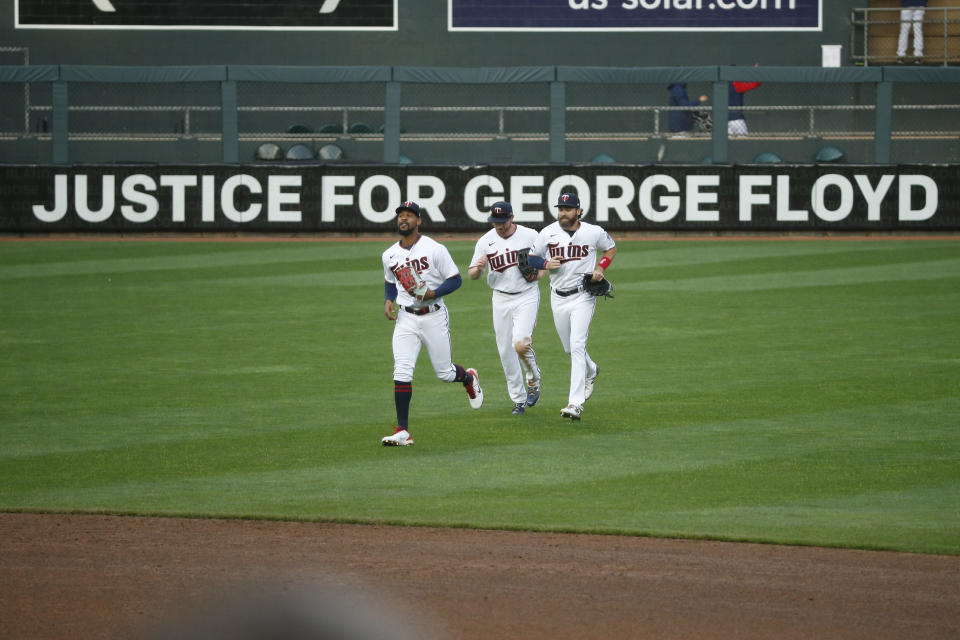 """Minnesota Twins' Byron Buxton, Kyle Garlick, and Jake Cave, left to right, celebrate the 10-2 win over Seattle Mariners in front of a Target Field sign that reads """"Justice for George Floyd"""" at a baseball game Thursday, April 8, 2021, in Minneapolis. (AP Photo/Bruce Kluckhohn)"""