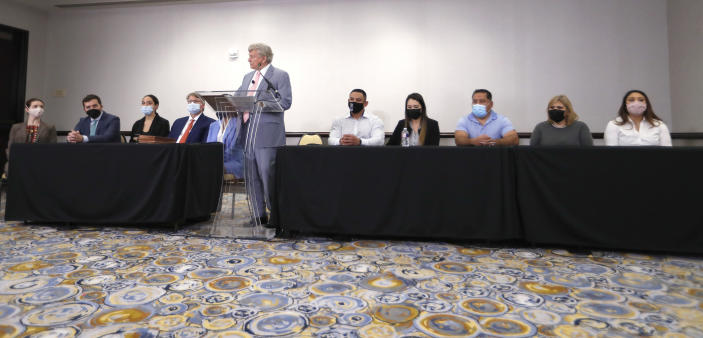 Houston Police officer Felipe Gallegos, fifth from right, listens as lawyer Rusty Hardin speaks during a press conference at Hilton Americas, Tuesday, Jan. 26, 2021, in Houston. Gallegos has been charged with murder and is among additional officers who have been indicted as part of an ongoing investigation into a Houston Police Department narcotics unit following a deadly 2019 drug raid, prosecutors announced Monday. (Karen Warren/Houston Chronicle via AP)