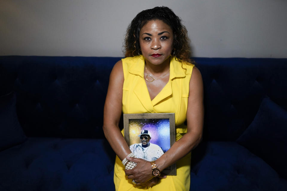 Daphne Bolton poses for a portrait holding a photograph of her brother at her home on Monday, May 31, 2021, in Charlotte, N.C. Bolton's brother, Johnny Lorenzo Bolton, a 49-year-old Black man was shot to death by a Cobb County Sheriff's Office SWAT team member serving a search warrant last December. (AP Photo/Chris Carlson)