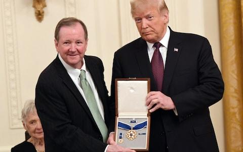Jack Soden, CEO of Elvis Presley Enterprises, accepts the Presidential medal of Freedom award - Credit: AFP