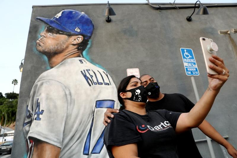LOS ANGELES, CA - SEPTEMBER 09: Ana and Brian Garcia take a selfie with the Los Angeles Dodgers pitcher Joe Kelly pouty face mural painted on the side of the Floyd's 99 Barbershop in Silver Lake, less than two miles from Dodger Stadium just in time for Astros series on Wednesday, Sept. 9, 2020 in Los Angeles, CA. (Gary Coronado / Los Angeles Times)