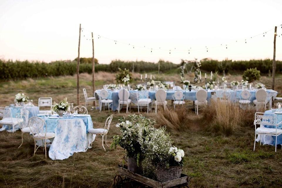 """""""A shot of the reception set-up right before dinner was served,"""" Nicholas says. """"Tall field grass creates natural aisles and paths to the different seating areas for guests to congregate."""""""