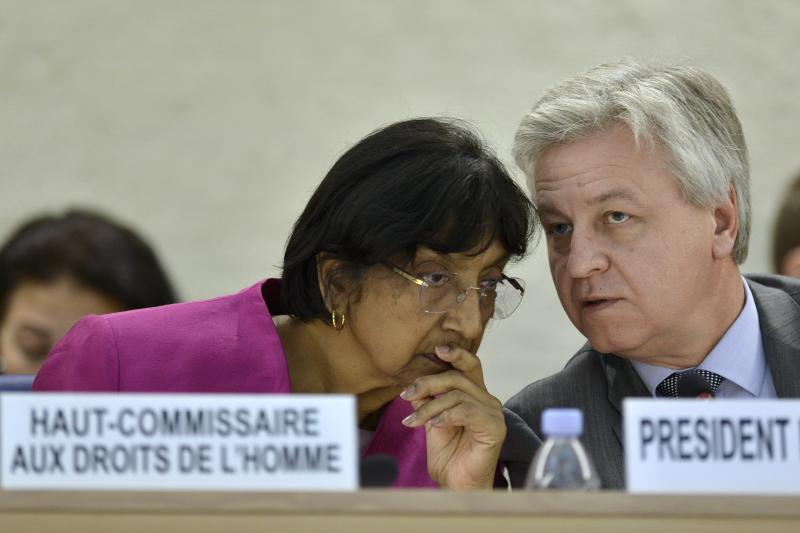 UN High Commissioner for Human Rights South African Navi Pillay, left, speaks with Polish Remigiusz Henczel, right, President of the Human Rights Council, during the urgent debate on the situation in Syria at the 23rd session of the Human Rights Council, at the European headquarters of the United Nations in Geneva, Switzerland, Wednesday, May 29, 2013. Syria's civil war is spilling out of control and represents a massive failure to protect citizens against war crimes and crimes against humanity that are now a routine occurrence according to the U.N.'s top human rights official Pillay. (AP Photo/Keystone, Martial Trezzini)