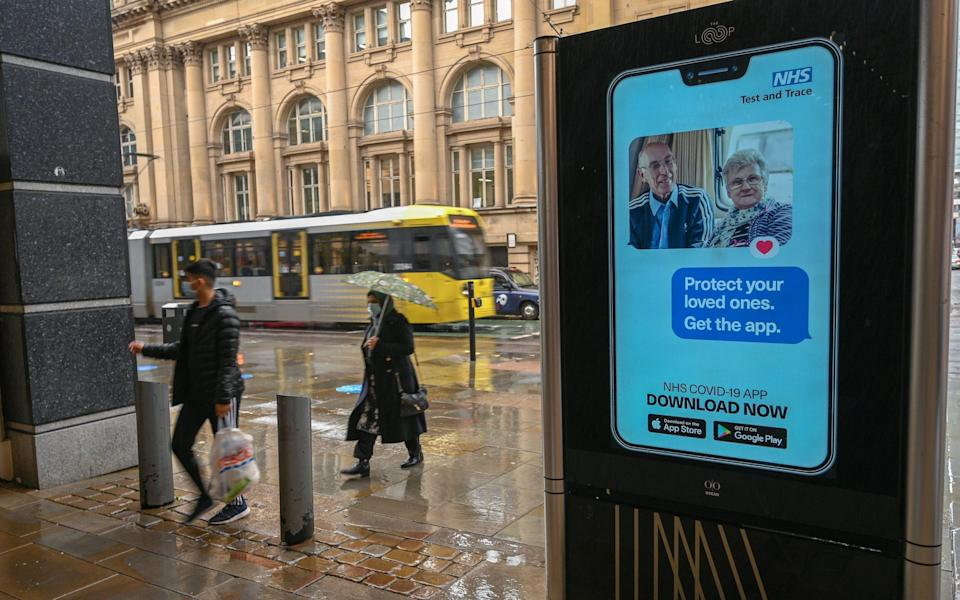 People walk past an electronic sign reminding pedestrians to download the NHS Test and Trace app in Manchester - Paul Ellis/AFP