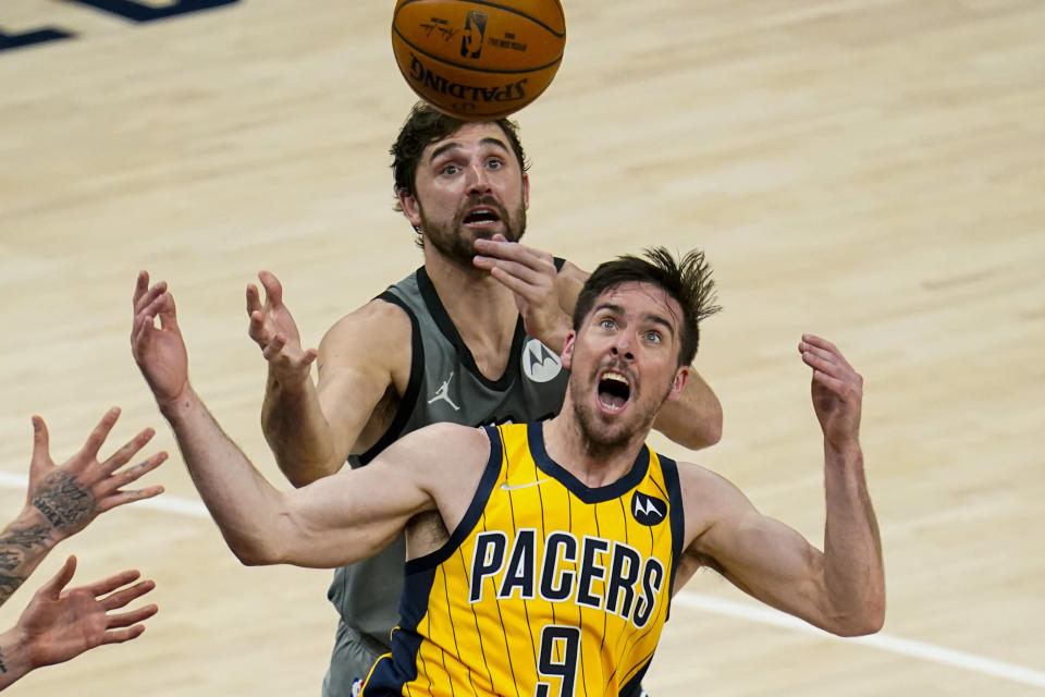 Indiana Pacers guard T.J. McConnell (9) and Brooklyn Nets forward Joe Harris go for a rebound during the first half of an NBA basketball game in Indianapolis, Wednesday, March 17, 2021. (AP Photo/Michael Conroy)