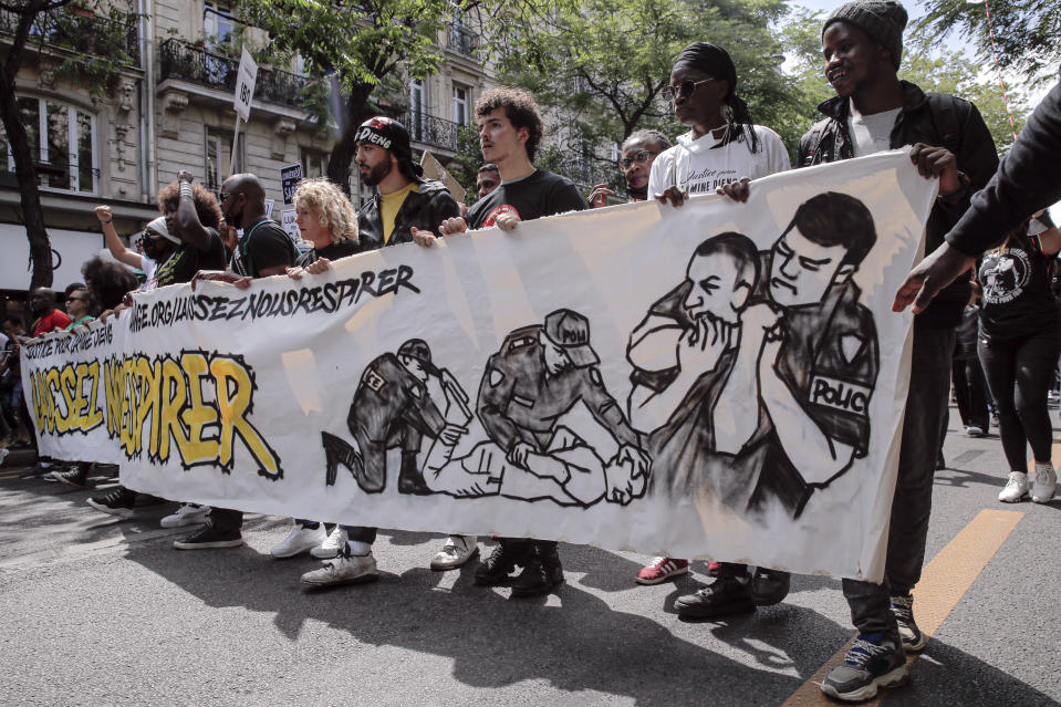 """People march holding a banner that reads """"Let us breathe"""" during a protest in memory of Lamine Dieng, a 25-year-old Franco-Senegalese who died in a police van after being arrested in 2007, in Paris, Saturday, June 20, 2020. Multiple protests are taking place in France on Saturday against police brutality and racial injustice, amid weeks of global anger unleashed by George Floyd's death in the US. (AP Photo/Christophe Ena)"""