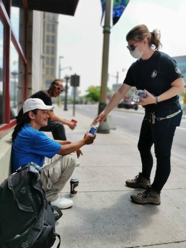 Salvation Army outreach workers hand out bottles of water to people experiencing homelessness on the street in Ottawa during the latest heat wave. (Submitted by Jason Pino - image credit)