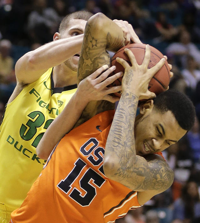Oregon State's Eric Moreland (15) is fouled by Oregon's Ben Carter as they wrestle for a rebound in the first half of an NCAA college basketball game in the Pac-12 men's tournament, Wednesday, March 12, 2014, in Las Vegas. (AP Photo/Julie Jacobson)