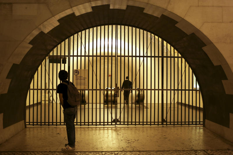 A man watches a security guard walk away after closing the gates of a subway station in downtown Lisbon at the start of a 24-hour strike Monday night, Oct. 7, 2013. The capital's subway will remain closed until Thursday morning while worker's unions go on strike to protest the privatization of public transport. (AP Photo/Armando Franca)