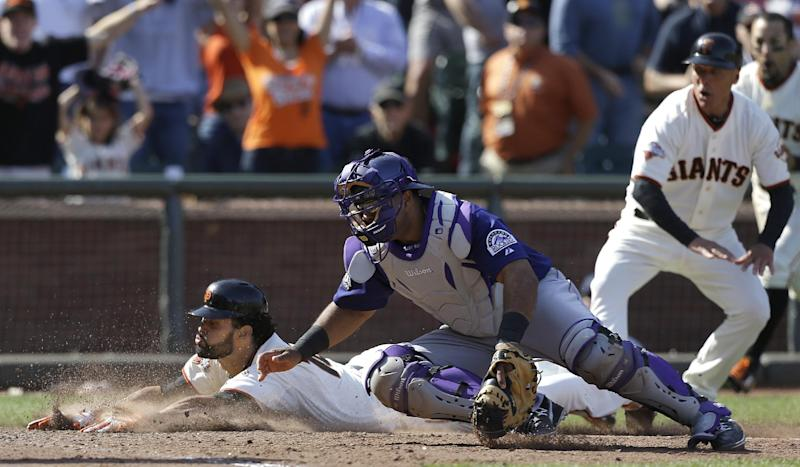 San Francisco Giants' Angel Pagan, left, slides past Colorado Rockies catcher Wilin Rosario to score on a two-run inside-the-park home run during the tenth inning of a baseball game in San Francisco, Saturday, May 25, 2013. The Giants won 6-5. (AP Photo/Jeff Chiu)
