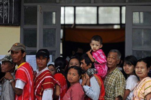 Voters stand in a queue outside a polling station in Kawhmu