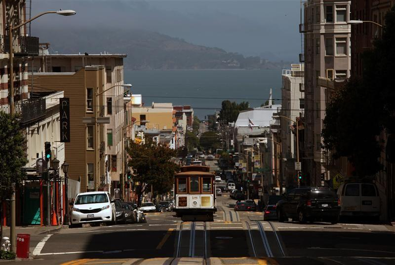 A cable car climbs Powell Street as it approaches California Street in San Francisco, California.