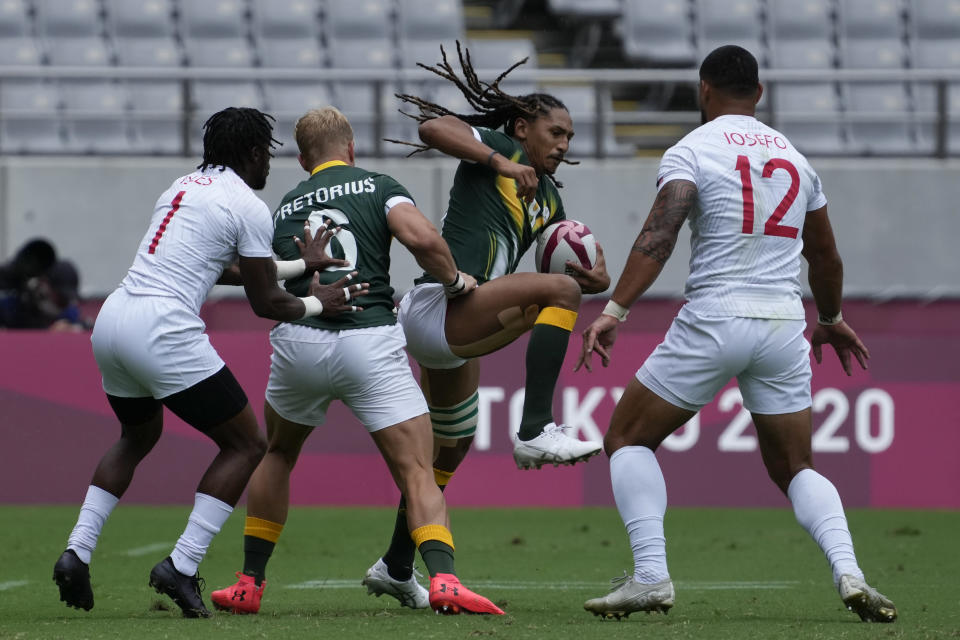 South Africa's Justin Geduld carries the ball past, from right, Martin Iosefo of the United States, South Africa's JC Pretorius, and Carlin Isles of the United States, in their men's rugby sevens match at the 2020 Summer Olympics, Tuesday, July 27, 2021 in Tokyo, Japan. (AP Photo/Shuji Kajiyama)