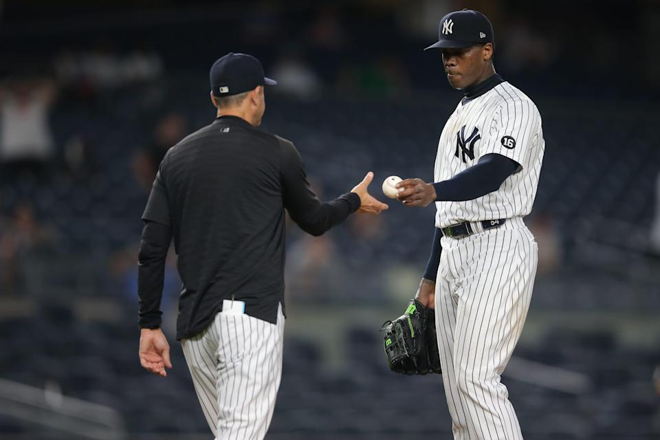 Yankees manager Aaron Boone (left) takes relief pitcher Aroldis Chapman (right) out of the game against the Los Angeles Angels during the ninth inning at Yankee Stadium.