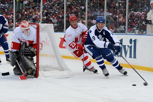 DETROIT, MI - DECEMBER 31: Tom Fergus #19 of the Toronto Maple Leafs controls the puck as Kevin Miller #23 of the Detroit Red Wings pursues and goaltender Kevin Hodson #31 defends the net in the first period during the 2013 Hockeytown Winter Festival Alumni Showdown on December 31, 2013 at Comerica Park in Detroit, Michigan. (Photo by Jamie Sabau/Getty Images)