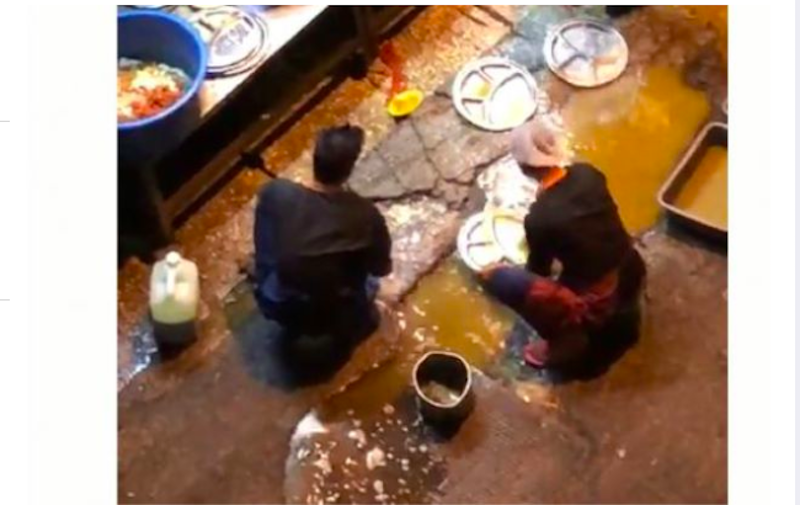 Screengrab of the restaurant's employees using water puddled beside a drain to clean dishes.