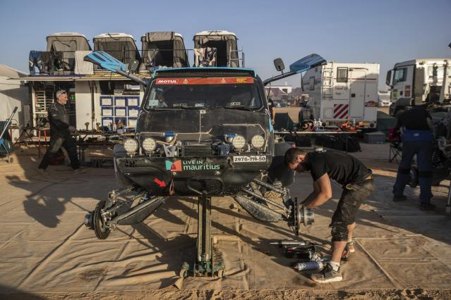 In this Monday, Jan. 13, 2020 photo, a mechanic works on a car after stage eight of the Dakar Rally in Wadi Al Dawasir, Saudi Arabia. Formerly known as the Paris-Dakar Rally, the race was created by Thierry Sabine after he got lost in the Libyan desert in 1977. Until 2008, the rallies raced across Africa, but threats in Mauritania led organizers to cancel that year's event and move it to South America. It has now shifted to Saudi Arabia. The race started on Jan. 5 with 560 drivers and co-drivers, some on motorbikes, others in cars or in trucks. Only 41 are taking part in the Original category. (AP Photo/Bernat Armangue)