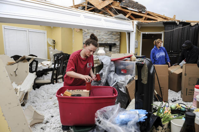 <p>Ivy Thigpen helps sort out kitchenware in Mike and Phillis Schell's destroyed house Tuesday, March 20, 2018, in Ardmore, Ala., after a violent storm went swept through the area the night before. (Photo: Jeronimo Nisa/The Decatur Daily via AP) </p>