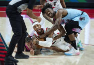 Miami Heat forward Jimmy Butler, right, and Portland Trail Blazers guard Damian Lillard look toward the referee after tying up with the ball during the first half of an NBA basketball game in Portland, Ore., Sunday, April 11, 2021. (AP Photo/Craig Mitchelldyer)