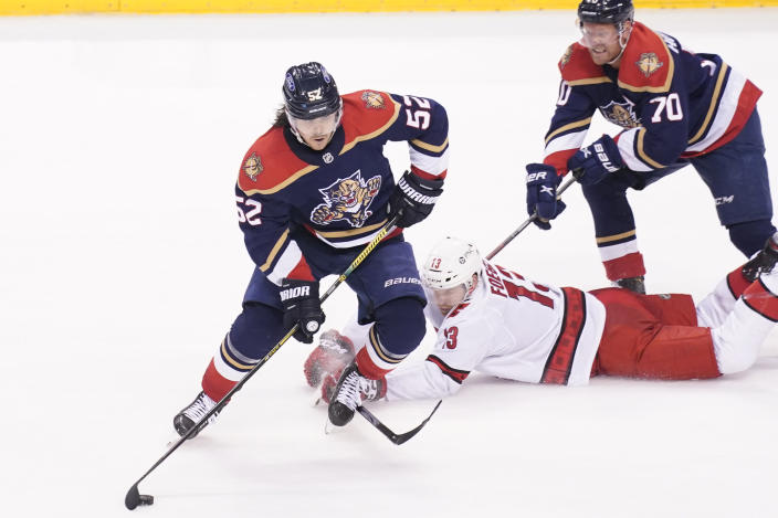 Florida Panthers defenseman MacKenzie Weegar (52) takes control of the puck from Carolina Hurricanes left wing Warren Foegele (13) during the second period at an NHL hockey game, Saturday, Feb. 27, 2021, in Sunrise, Fla. (AP Photo/Marta Lavandier)