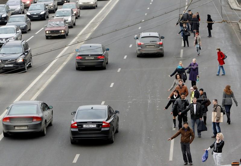FILE PHOTO: People hail taxis near the exit of Park Kultury metro station during a train service disruption in Moscow
