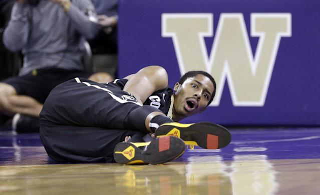 Colorado's Spencer Dinwiddie looks up after falling to the court against Washington with an injury in the first half of an NCAA college basketball game, Sunday, Jan. 12, 2014, in Seattle. (AP Photo/Elaine Thompson)